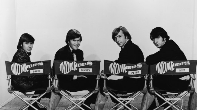 Promotional portrait of popular music and television group the Monkees, dressing in tuxedos and they as they sit in folding chair and look over their shoulders, early 1970s. From left,  British musician and actor Davy Jones, and American musician and actors Mickey Dolenz, Peter Tork, and Michael Nesmith. The chairs are labeled with the band's guitar-shaped logo and the name of each member. (Photo by NBC Television/Courtesy of Getty Images)